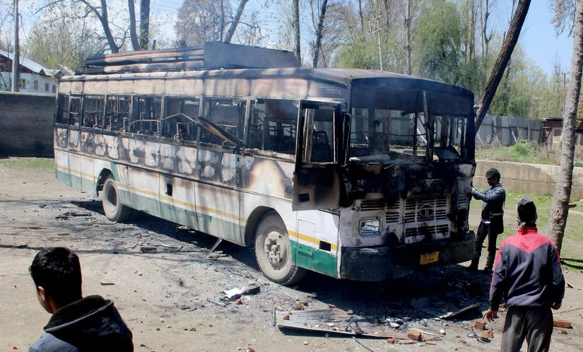 A charred polling staff bus following an attack by a group of protesters at Nowgam during voting for Srinagar bypoll. PTI