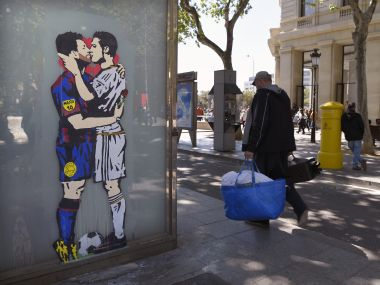 "People pass next to the street art ""Love is blind"" which shows Lionel Messi and Cristiano Ronaldo kissing each other. AFP"