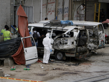 Pakistani investigators examine damage vehicles at the site of suicide bombing in Lahore, Pakistan, Wednesday on Wednesday. AP