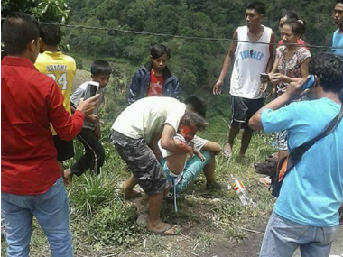 Volunteers try to rescue an injured passenger after a bus apparently lost its brakes and plunged into a deep ravine killing dozens in Carranglan township, Nueva Ecija province in northern Philippines Tuesday, April 18, 2017.