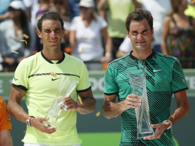 Rafael Nadal and Roger Federer hold their trophies  after Federer won the Miami Open title. AP