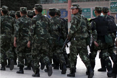 Armed police officers patrol an ethnic Uighur area in Kashgar, in Xinjiang province. Reuters