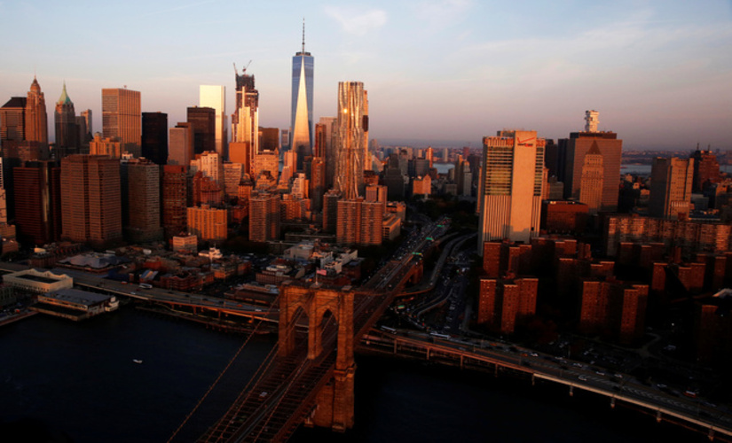 The sun rises over Brooklyn, NY with a view of the iconic Brooklyn bridge/ Reuters