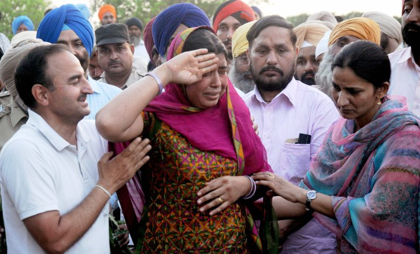 Wife of a CRPF martyr saluting her husband's body at his funeral in a village in Punjab. PTI