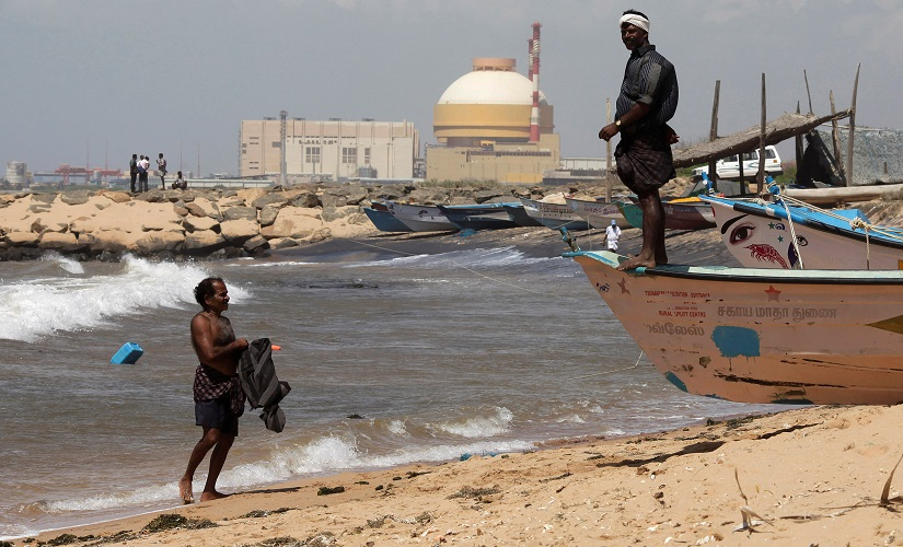 A fisherman stands on his boat on a beach near Kudankulam nuclear power. Reuters