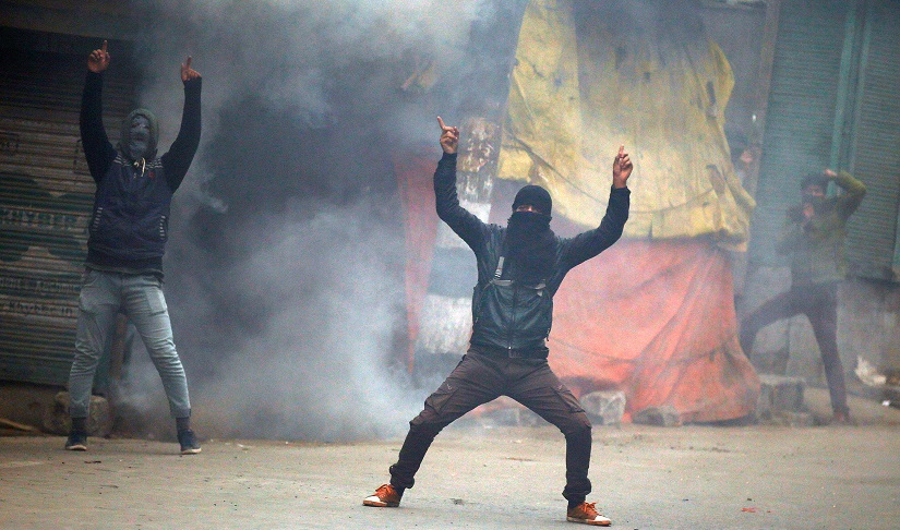 Masked protesters shout pro-freedom slogans amid smoke from a tear gas shell in Kashmir. Reuters