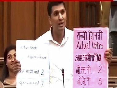 AAP leader Saurabh Bharadwaj in the Delhi Assembly demonstrating the 'faulty' EVMs. PTI