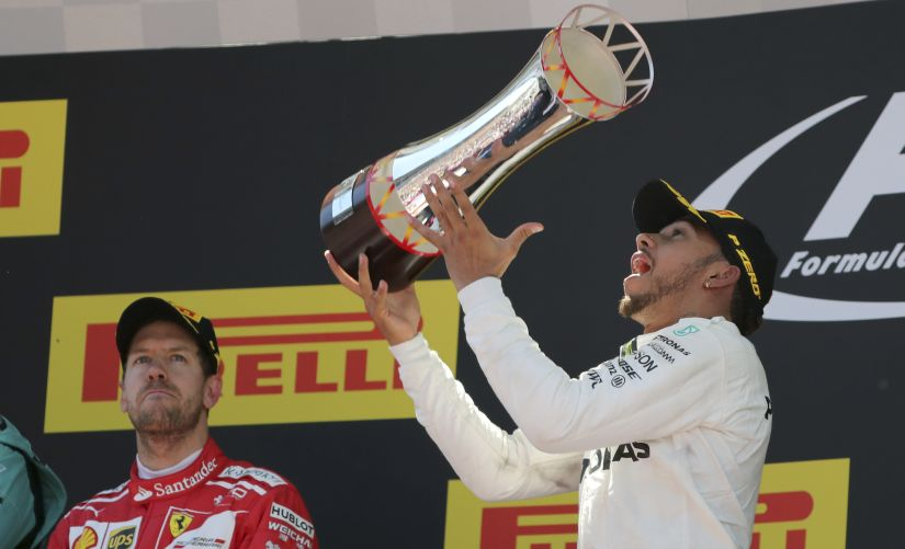Mercedes driver Lewis Hamilton celebrates on the podium after winning the Spanish Grand Prix. AP