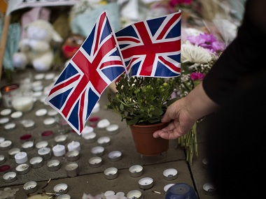 A woman places flowers in Albert Square in Manchester, Britain, Wednesday, May 24, 2017, after the suicide attack at an Ariana Grande concert that left more than 20 people dead and many more injured, as it ended on Monday night at the Manchester Arena. (AP Photo/Emilio Morenatti)
