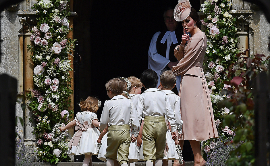 Britain's Catherine, Duchess of Cambridge (R) gestures as she walks with the bridesmaids and pageboys as they arrive for her sister Pippa Middleton's wedding to James Matthews at St Mark's Church in Englefield, west of London, on May 20, 2017. Pippa Middleton hit the headlines with a figure-hugging outfit at her sister Kate's wedding to Prince William but now the world-famous bridesmaid is becoming a bride herself. Once again, all eyes will be on her dress as the 33-year-old marries financier James Matthews on Saturday at a lavish society wedding where William and Kate's children will play starring roles. AP