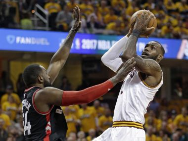 Cleveland Cavaliers' LeBron James, right, drives to the basket against Toronto Raptors. AP