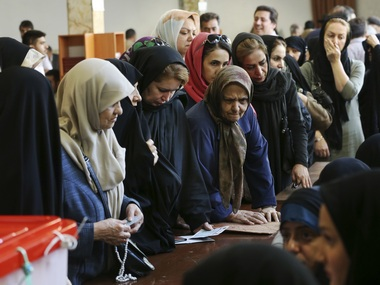 Voters wait to cast their ballots in the presidential and municipal council election in Tehran, Iran. AP