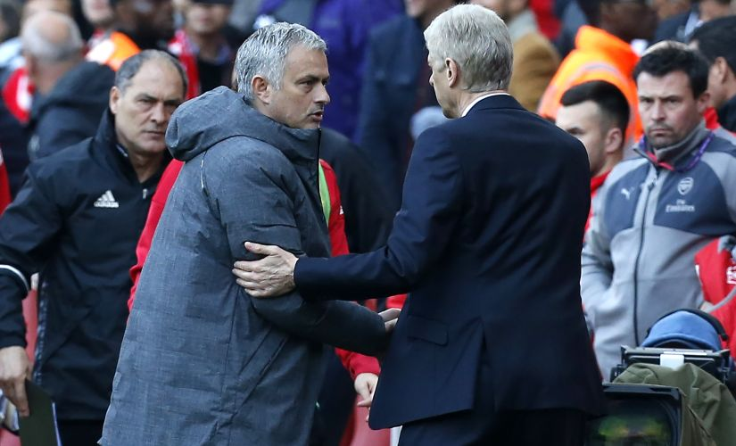 Arsenal's manager Arsene Wenger shakes hands with Manchester United's manager Jose Mourinho (2nd L) after Arsenal's win. AFP