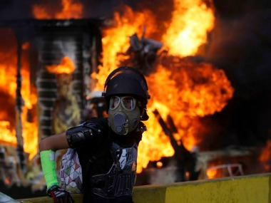 A truck burns in the background as a masked protester eyes a security forces cordon during protests in Venezuela. AP