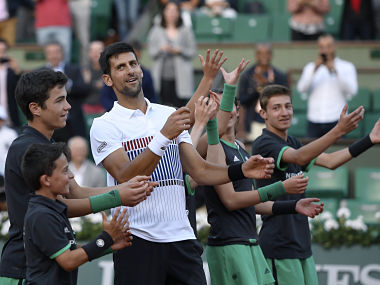 Serbia's Novak Djokovic dances with the ball boys as he celebrates after winning against Spain's Albert Ramos-Vinolas during their tennis match at the Roland Garros 2017 French Open on June 4, 2017 in Paris. / AFP PHOTO / Eric FEFERBERG