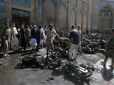 Men remove the burnt motorbike from the site of an explosion in western Herat city on Tuesday. AP