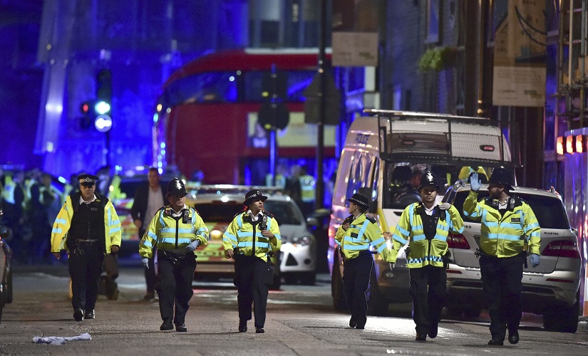 Police officers on Borough High Street investigate the attack on Saturday night. AP