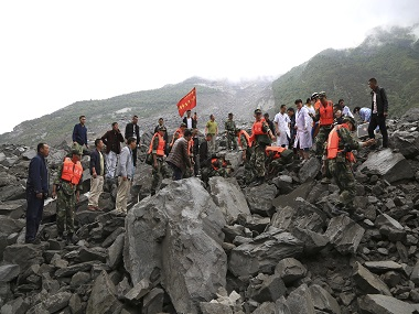 Emergency personnel work at the site of a landslide in Maoxian County in China's Sichuan Province. AP