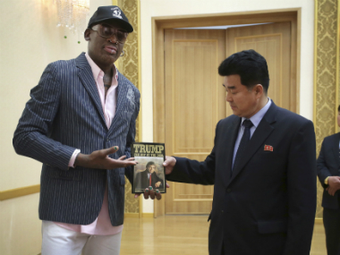 "Former NBA basketball star Dennis Rodman presents a book titled ""Trump The Art of the Deal"" to North Korea's Sports Minister Kim Il Guk. AP"