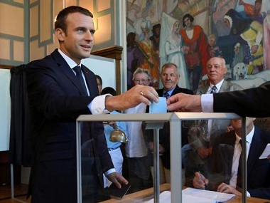 French President Emmanuel Macron casts his ballot as he votes at a polling station in the second round parliamentary elections. Reuters