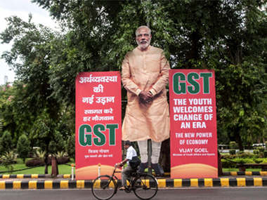 A man cycles past a huge cutout of Prime Minister Narendra Modi, next to Goods and Services Tax (GST) banners in New Delhi, on Friday. PTI