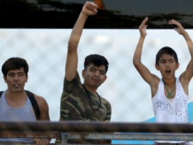 File image of Migrants wave to the media during a police operation to evacuate an unused terminal building of the old international airport. AP
