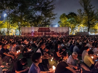 Participants hold candles as the Tiananmen Square banner stands at the background at Victoria Park on June 4, 2017 in Hong Kong, Hong Kong on the 28th anniversary of the massacre. Getty Images
