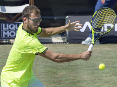 Jerzey Janowicz of Poland returns the ball to Grigor Dimitrov of Bulgaria during their match at the Mercedes Cup tennis tournament in Stuttgart