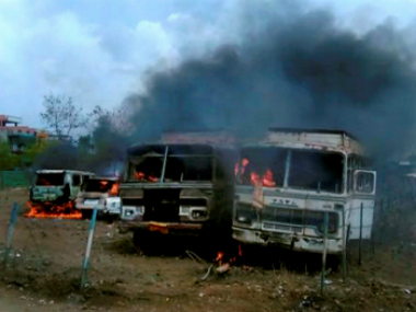 Buses torched by the agitating farmers on Bhopal-Indore highway in Dewas district on Wednesday. PTI