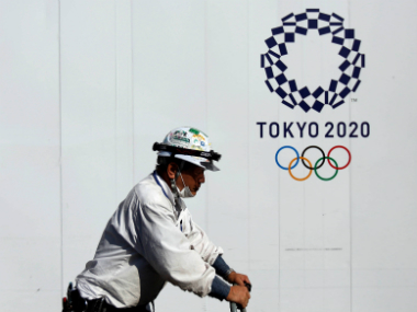 A construction worker walks past a 2020 Olympics building construction site in Tokyo. Reuters
