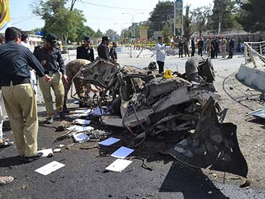 Pakistani police officers examine the site of an explosion in Quetta, Pakistan. AP