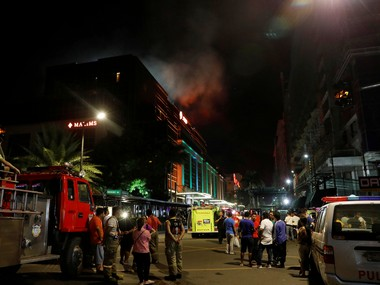 Evacuated employees watch as smoke billows from Resorts World Manila casino in Philippines. Reuters