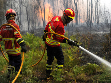 Portuguese firefighters work to stop a forest fire from reaching the village of Figueiro dos Vinhos central Portugal, Sunday