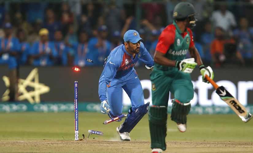India's captain MS Dhoni dashes to catch Bangladesh's Mustafizur Rahman just short. India win by 1 run to progress into the knockouts. Reuters