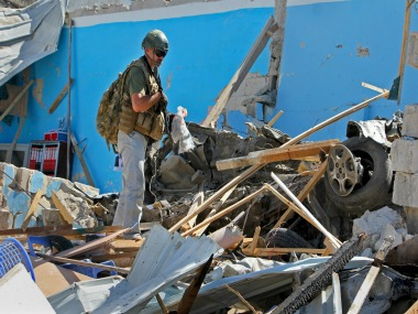 A foreign security personnel examining the site of the blast. AP