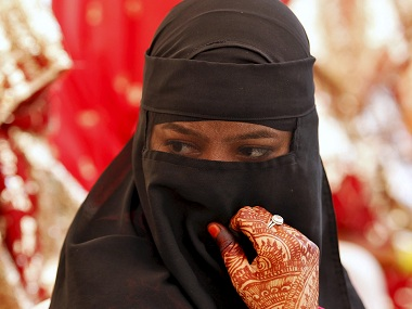 A veiled Muslim bride waits for the start of a mass marriage ceremony in Ahmedabad, India, October 11, 2015. A total of 65 Muslim couples from various parts of Ahmedabad on Sunday took wedding vows during the mass marriage ceremony organised by a Muslim voluntary organisation, organisers said. REUTERS/Amit Dave - RTS3Z5U