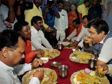 Union Minister for Road Transport and Highways and Shipping Nitin Gadkar having meal at a Dalit's house at Harmu in Ranchi on Thursday. PTI