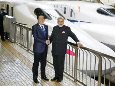 Narendra Modi and Shinzo Abe pose in front of a Shinkansen Bullet train at Tokyo Station. Reuters