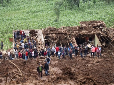 Residents stand at a house damaged by a mudslide in San Pedro Soloma, Guatemala. Reuters