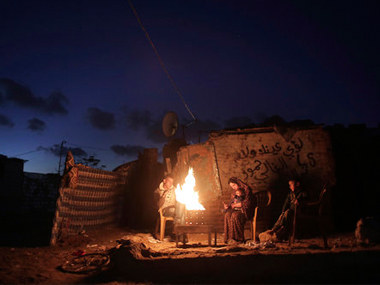 File image of a Palestinian family warm themselves up with a fire outside their makeshift house during a power cut in a poor neighborhood in Gaza. AP