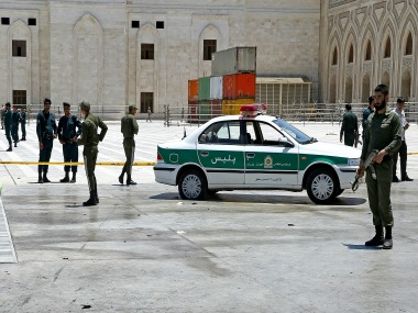 Police officers control scene after terror attacks in Tehran. AP