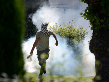A protester throws tear gas shell at the police during clashes in Srinagar on Friday. PTI
