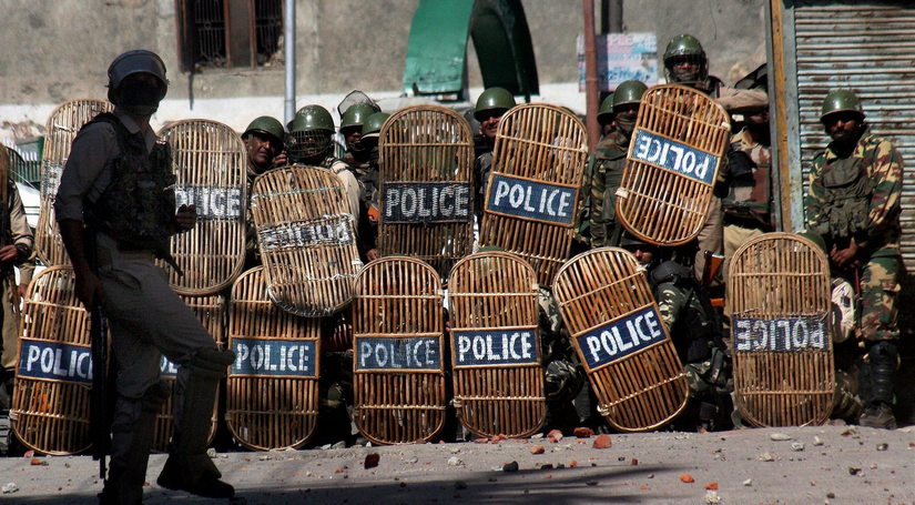 Security personnel cover themselves with shields during clashes with the youths on Friday. PTI