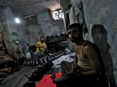 A shoe-maker poses for a picture in an underground workshop in Agra, India. Reuters