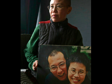 In this Dec. 6, 2012 file photo, Liu Xia, wife of 2010 Nobel Peace Prize winner Liu Xiaobo, poses with a photo of her and her husband during an interview at her home in Beijing. Jailed Chinese Nobel peace laureate and dissident Liu has been released on medical parole after being diagnosed with late-stage liver cancer, his lawyer said Monday, June 26, 2017.