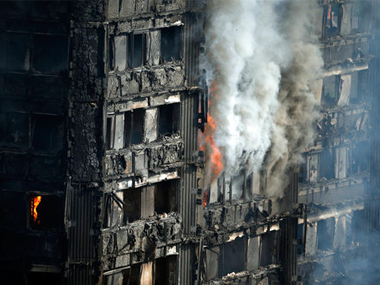 Parts of the building still burn hours after a deadly blaze at a high rise apartment block in London, Wednesday. AP
