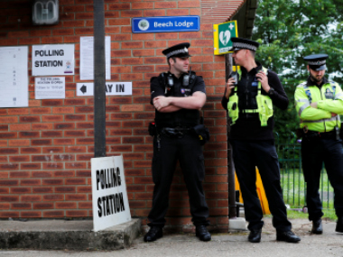 Police officers stand on duty outside a polling station in Sonning, Britain. Reuters
