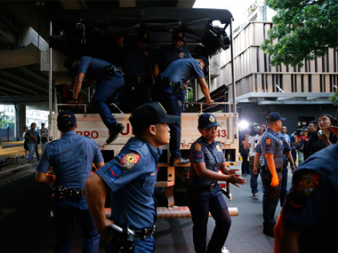 Police alight from their vehicle outside a hotel at the Resorts World Manila complex on early Friday after a gunman killed 37 people. AP