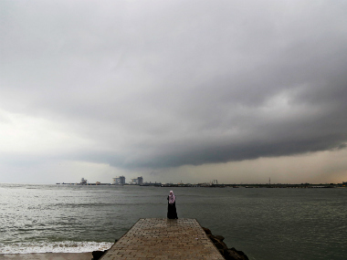 A woman stands on a seaside promenade against the background of pre-monsoon clouds over the Arabian Sea in Kochi, India. Reuters