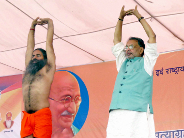 File image of Union agriculture minister Radha Mohan Singh (right) performing Yoga with Baba Ramdev (left). PTI